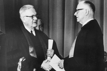 Evangelical United Brethren Church Bishop Reuben H. Mueller (left) and Methodist Bishop Lloyd C. Wicke join hands on April 23, 1968, symbolizing the merger between the two denominations. 1968 file photo courtesy of the United Methodist Commission on Archives and History; cropped from original.