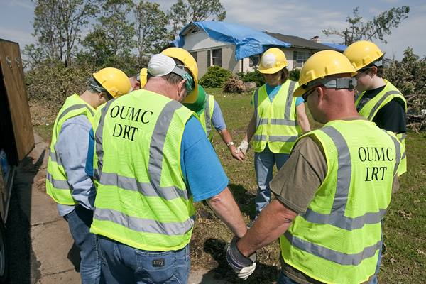 Volunteers from Ozark (Mo.) United Methodist Church's disaster response team pray before beginning to clear storm damage in Joplin, Mo. File photo by Mike DuBose, United Methodist Communications.