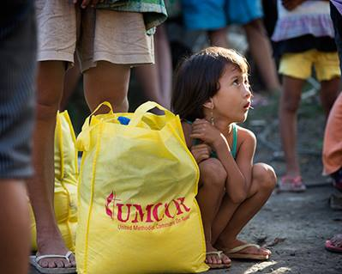 image_of_child_squatting_beside_yellow_umcor_bag
