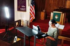 The Rev. Amy Wilson Feltz, pastor of St. Paul's United Methodist Church in El Paso, Texas, sets up computer equipment to stream a live sermon in the church's sanctuary in September. Although the pulpit, which is visible on-camera, has the appropriate liturgical color, the banner on the wall was from Lent, when the church had to suspend in-person worship. Photo courtesy of the Rev. Amy Wilson Feltz.